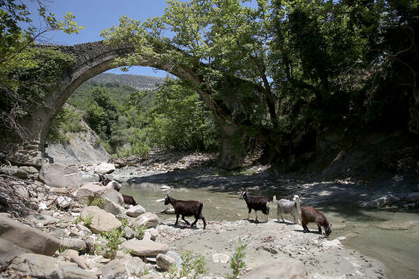 Trail riding in Albania, with a river and bridge