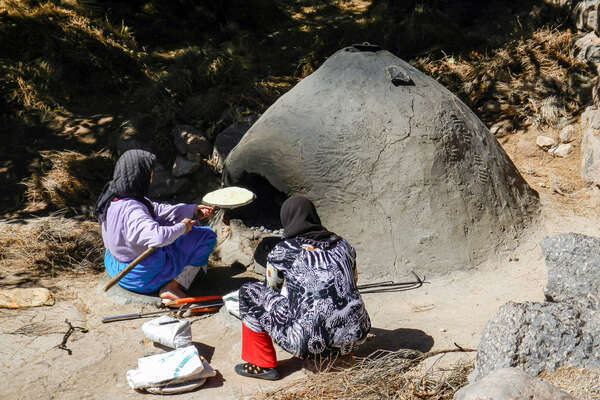 Two Moroccan women preparing food in a clay oven
