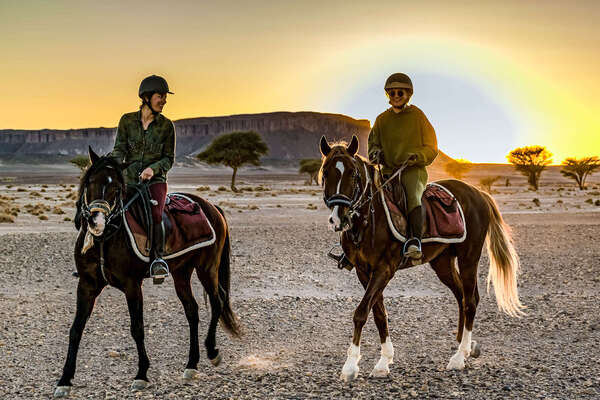 Two riders at sunset in the Sahara