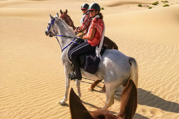Two riders riding in the dunes