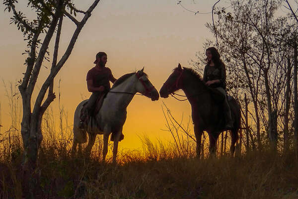 Two riders riding out a sunset in Costa Rica
