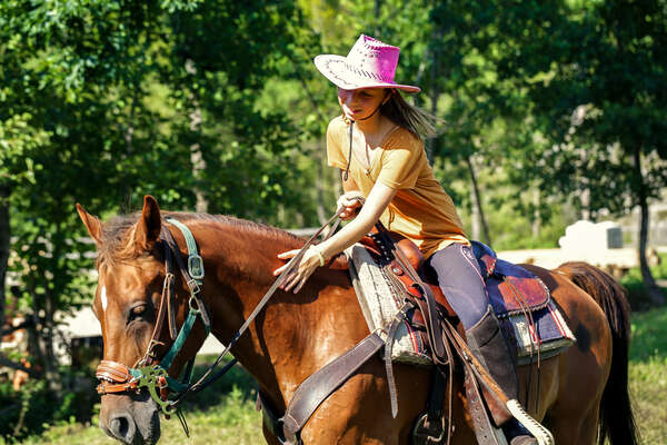Young girl riding a horse in a western saddle in Croatia